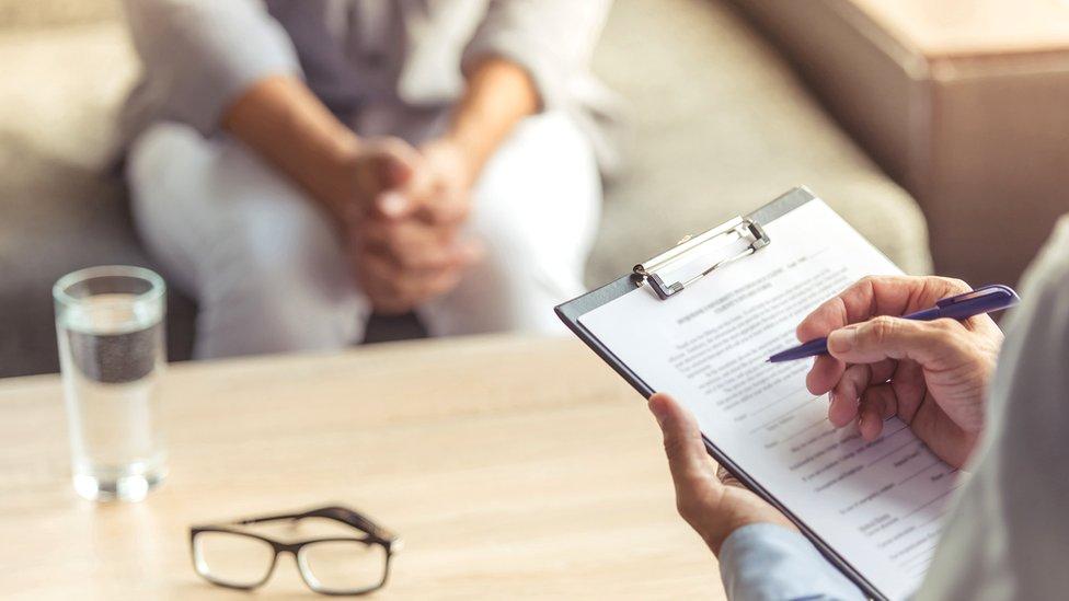 Detalle de libreta de notas y extremidades de doctor y paciente en una consulta.