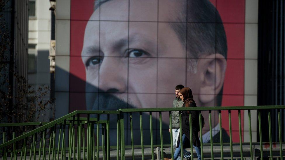 Una pareja camina frente a un gigantesco letrero con la imagen de Erdogan.