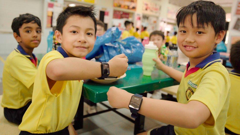 Los alumnos de la Escuela Secundaria del Almirantazgo en Singapur muestran sus nuevos relojes inteligentes con los que realizan compras en internet. (Foto: POSB -Banco de Singapur)