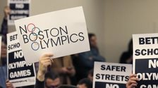 People hold up placards against the Olympic Games coming to Boston, during the first public forum regarding the city's 2024 Olympic bid, in Boston. 5 Februay 2015