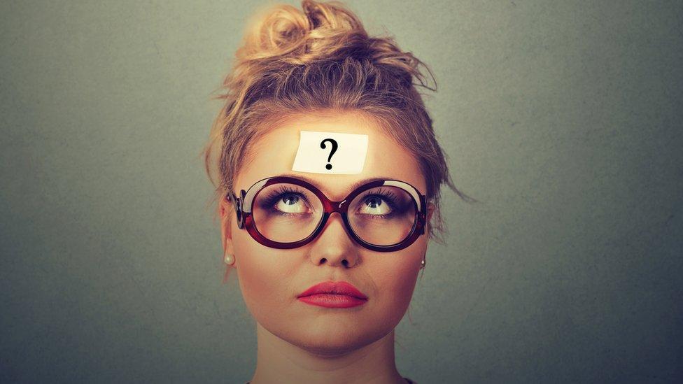 Mujer con signo de interrogación en la cabeza.