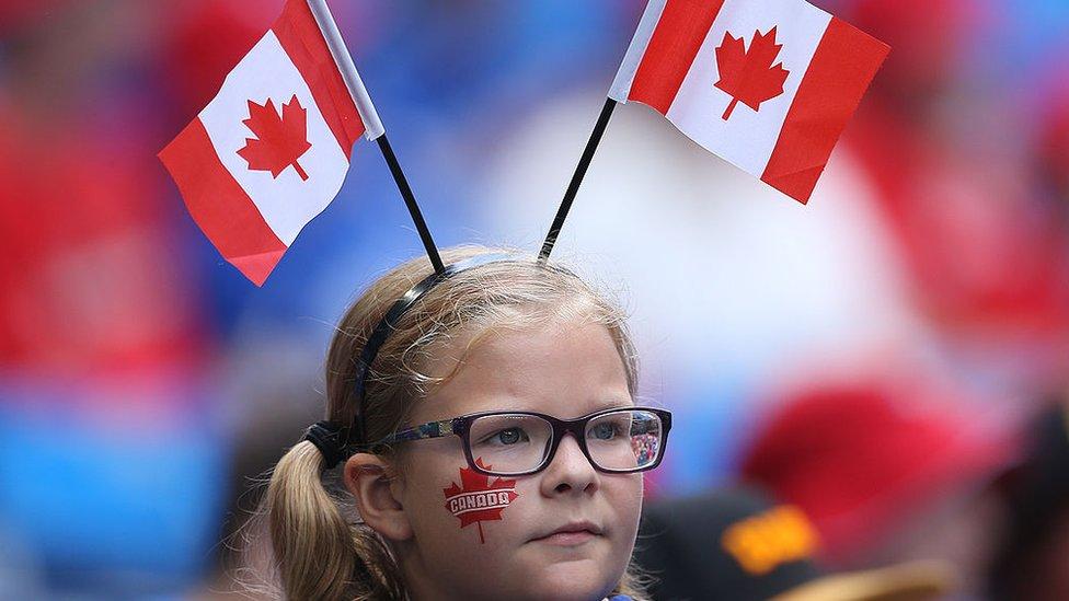 Una niña con banderas de Canadá.