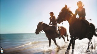 two women riding horses on the beach