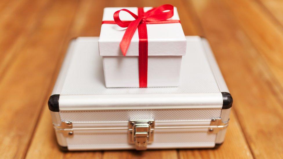 Un maletín con una caja de regalo encima.