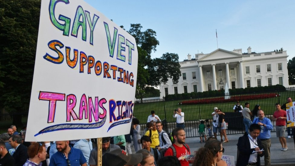 A sign is pictured with picketers outside the White House on Saturday