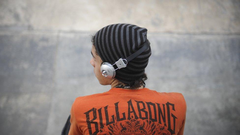 Skateboarder listens to music through headphones in Carracas, 2011