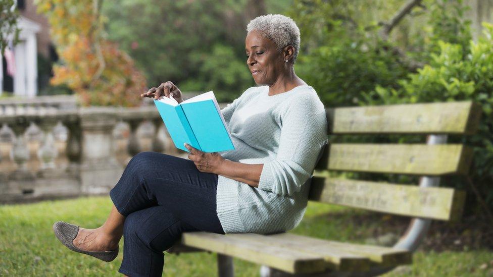 Una mujer sentada leyendo en un banco en un parque
