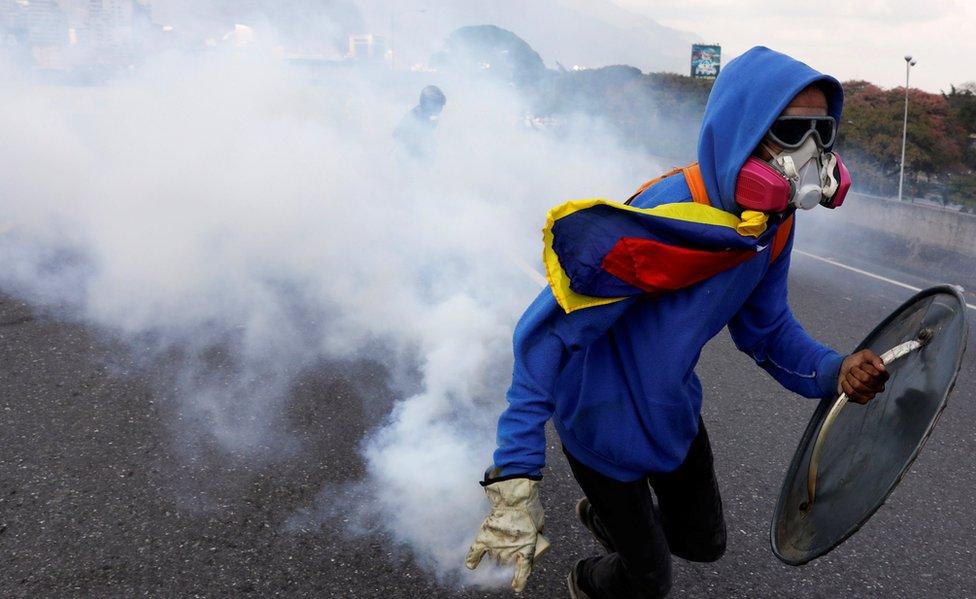 Activista venezolano devuelve un gas lacrimógeno.