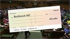 Graphic of a cheque over House of Commons