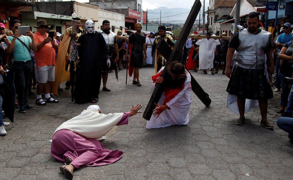 Persona cargando una cruz representando la