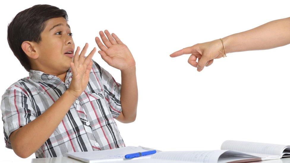 Una mano señalando a un niño