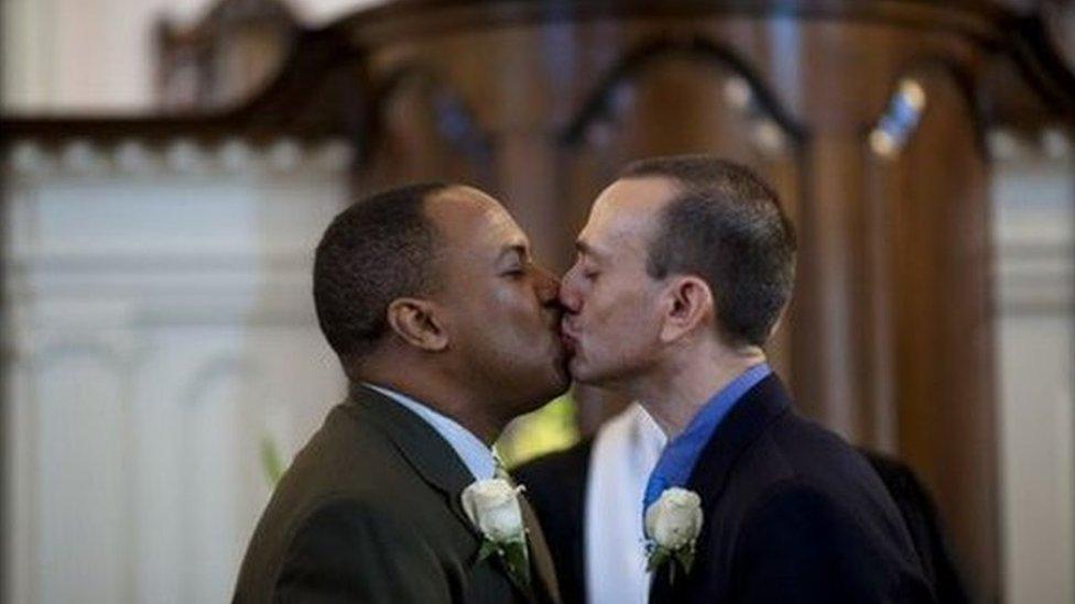 Two men kissing at altar