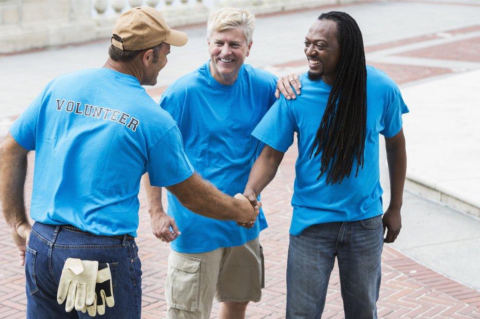 Tres voluntarios se saludan.