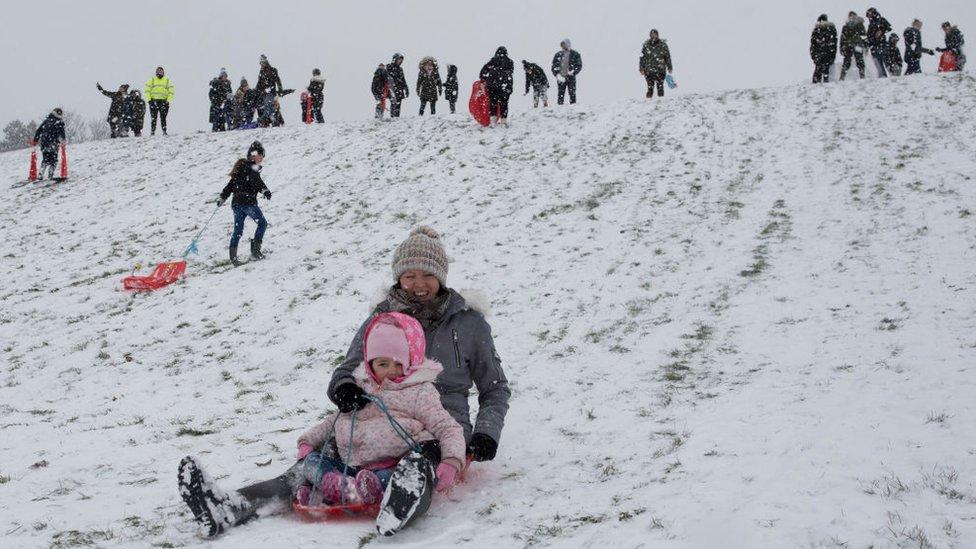 Gente disfrutando de la nieve en Inglaterra.