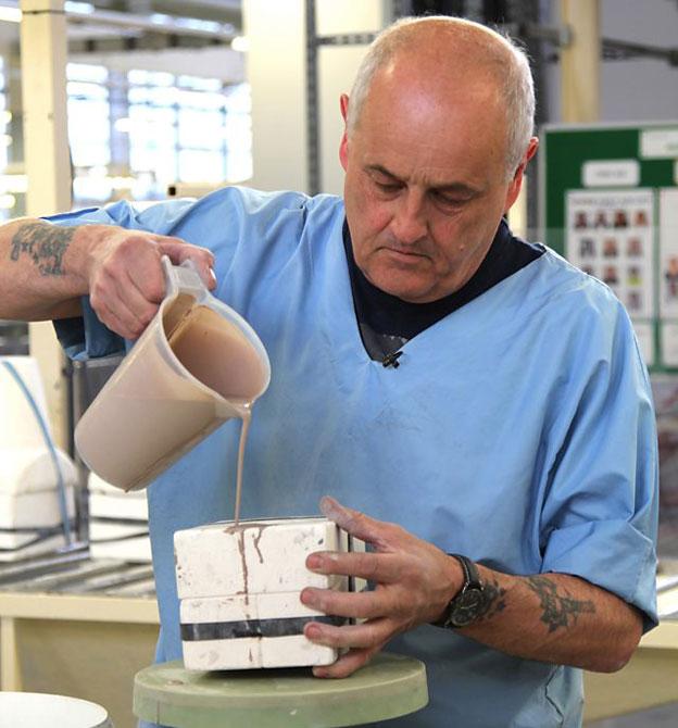 Para hacer las figurillas de pantera que dan nombre a la pieza Jeff Pettitt vierte arcilla líquida en un molde.