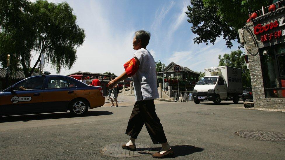 Una anciana vigila las calles de Pekín como voluntaria.