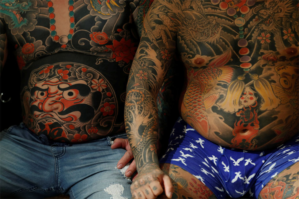 Two men sit next to each other with heavily tattooed torsos