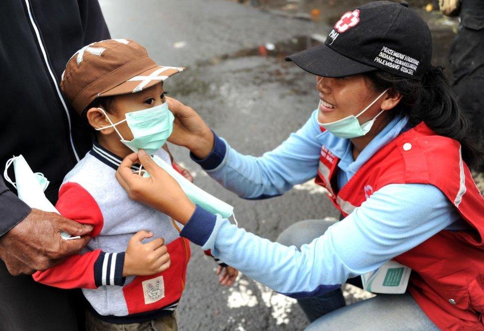 Una voluntaria le pone una mascarilla a un niño.