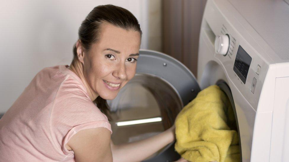 Una mujer metiendo ropa en una lavadora