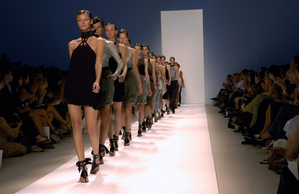 Models on a catwalk in a line