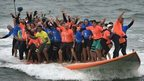 Sixty-six surfers from Huntington Beach ride the world's largest surfboard