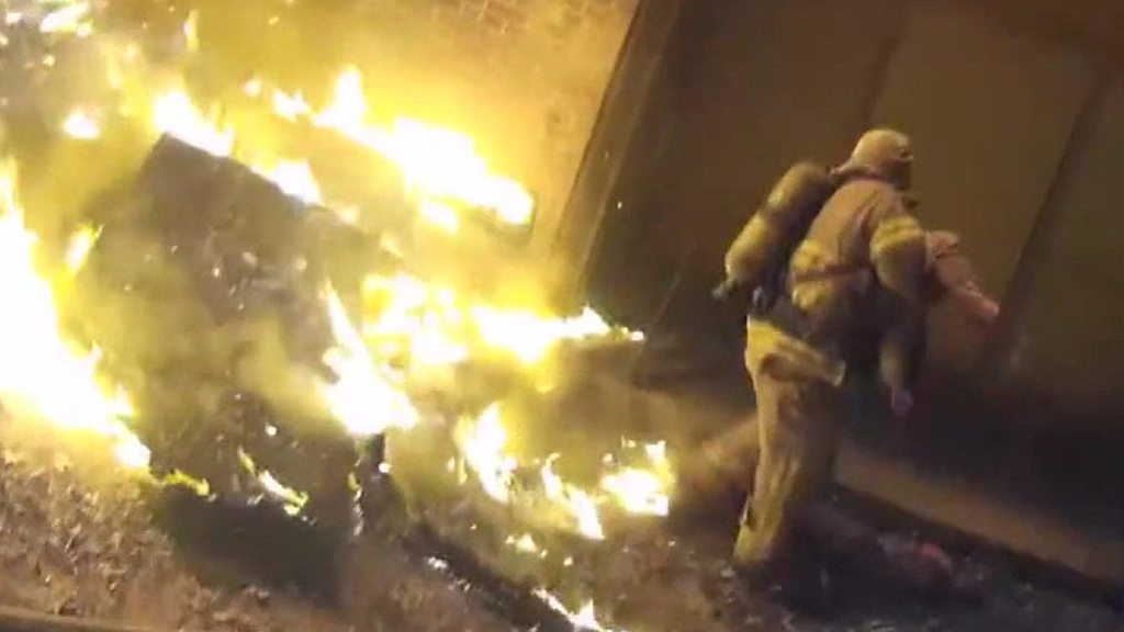 Firefighter catches child from burning building
