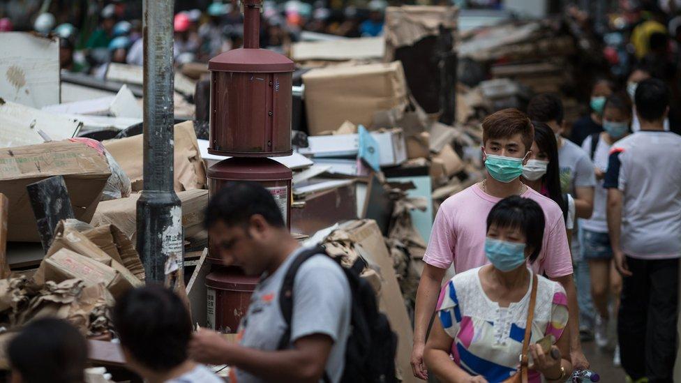 戴著口罩的澳門居民走過堆積如山的災後垃圾(25/8/2017)