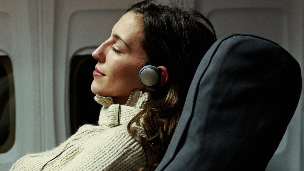 mujer escuchando música en avión