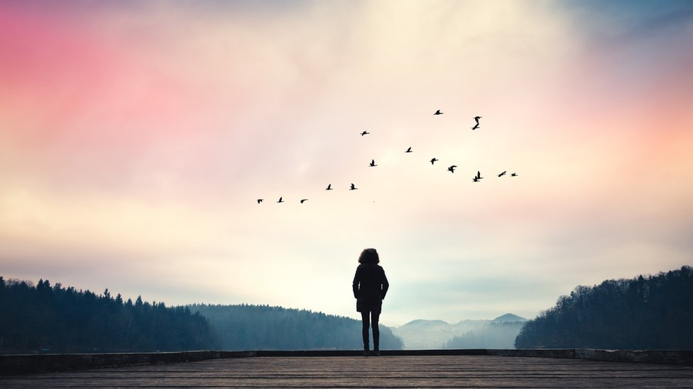 Mujer al borde de un lago sola