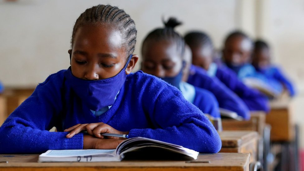 A schoolgirl wears a face mask as she reads a book inside a classroom at the Olympic Primary School during the partial reopening of schools, after the government scrapped plans to cancel the academic year due to the coronavirus disease (COVID-19) pandemic, in Kibera slums of Nairobi, Kenya October 12, 2020.