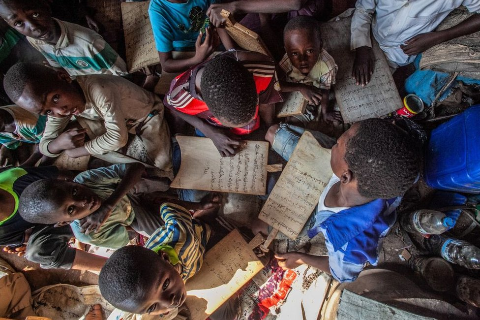 Children hold wooded boards of Koranic verse in a cramped, makeshift classroom.