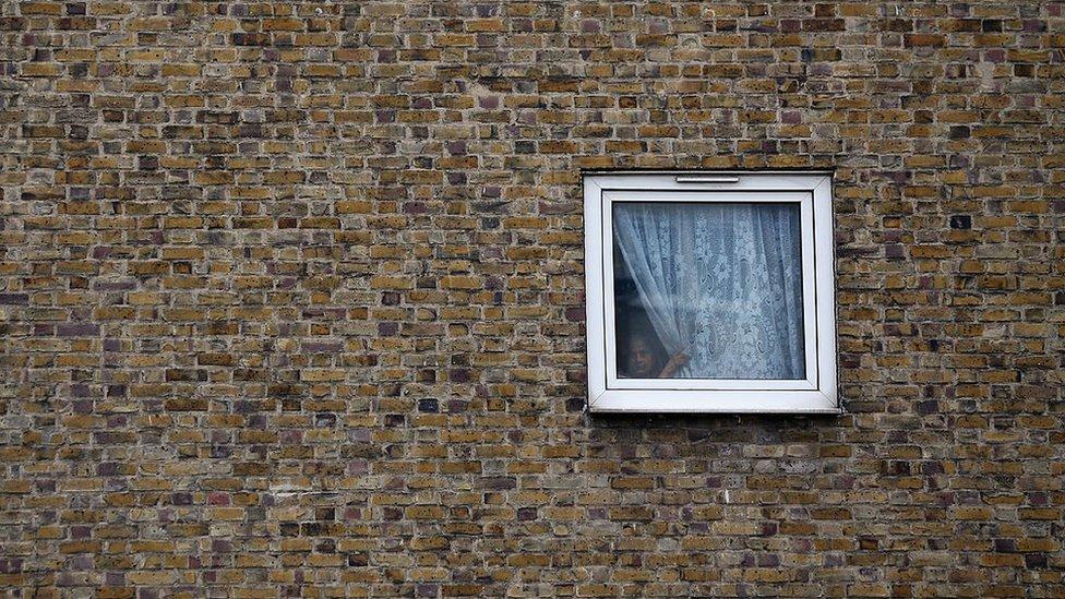 Una niña mira por la ventana de una vivienda social de Tower Hamlets, en el este de Londres.