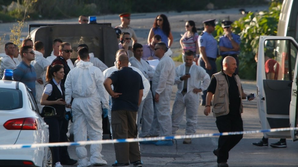 Police and forensics experts stand behind a road block after a powerful bomb blew up a car killing investigative journalist Daphne Caruana Galizia in Bidnija, Malta, 16 October 2017