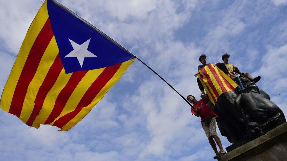 Manifestantes con una enorme bandera catalana independentista en Barcelona.