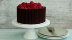 Cake decorated with chocolate sticks and raspberries