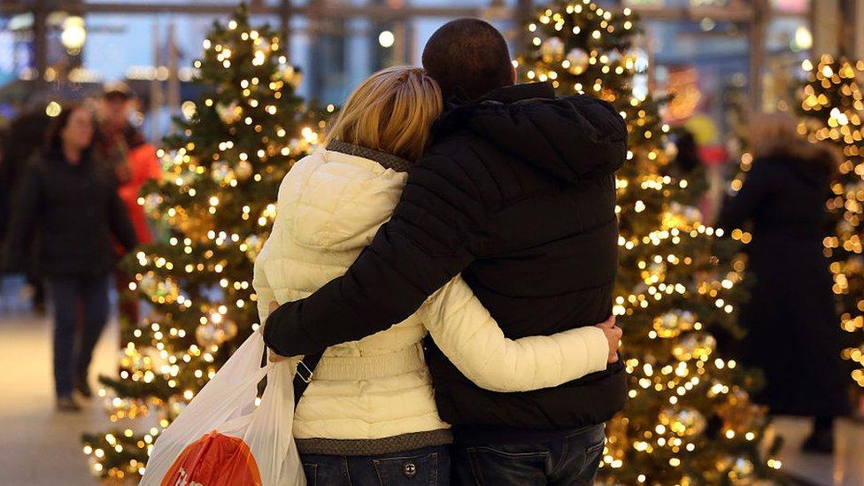 Pareja abrazada en un shopping frente a un árbol de Navidad.