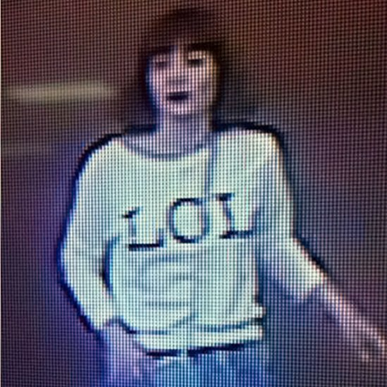 "Grainy image shows a woman with brown hair wearing a T-shirt with the letters ""LOL"""