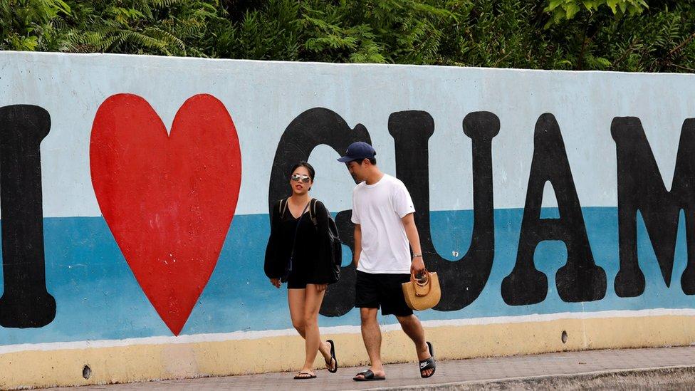 Turistas caminan por delante de un cartel que dice, en inglés,