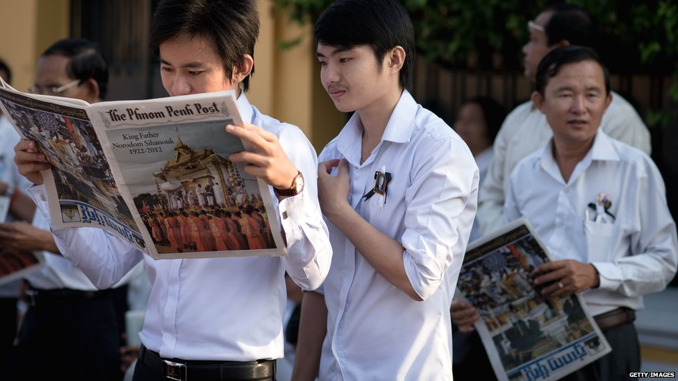 Men read newspapers as they wait outside the Royal Palace in the Cambodian capital Phnom Penh before being paying their final respects to former King Norodom Sihanouk on 2 February 2013.