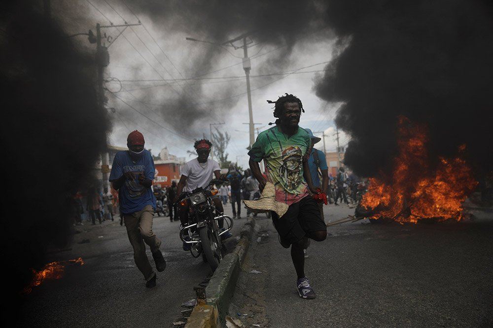 Protesters run past burning tyres