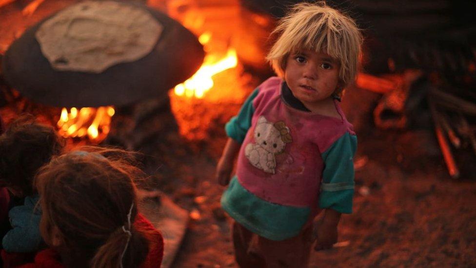 Un niño sirio mira a la cámara en un campo de refugiados.