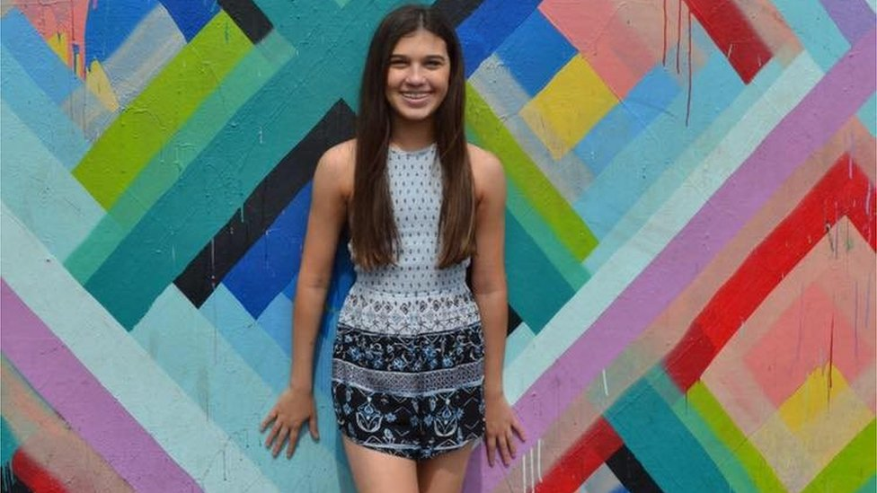 A teenage girl stands against a bright wall and smiles. Jaime Guttenberg/Facebook