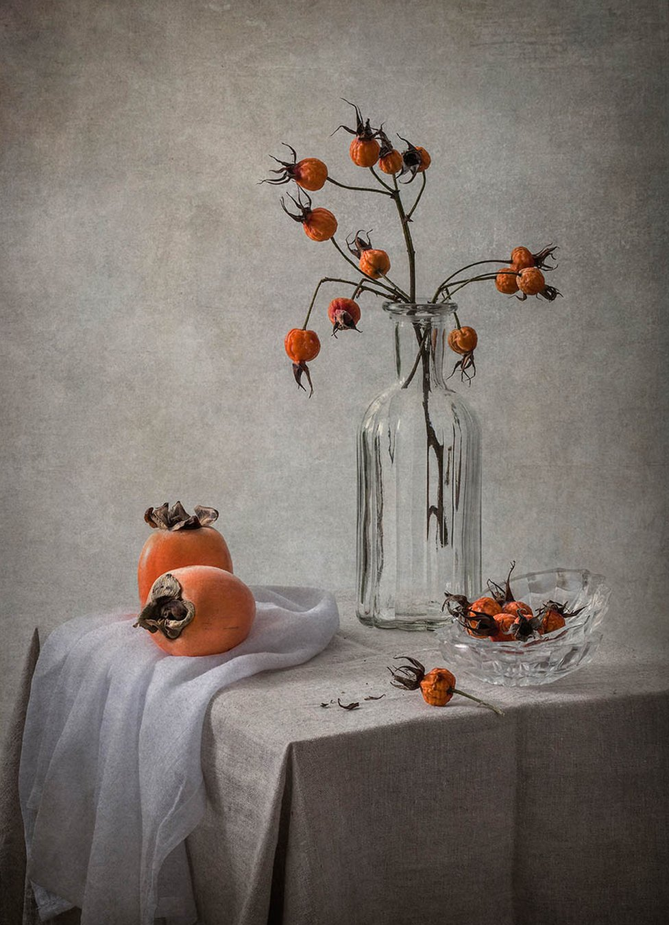 Rose hips in a glass vase with ripe persimmon fruits on table with a grey tablecloth
