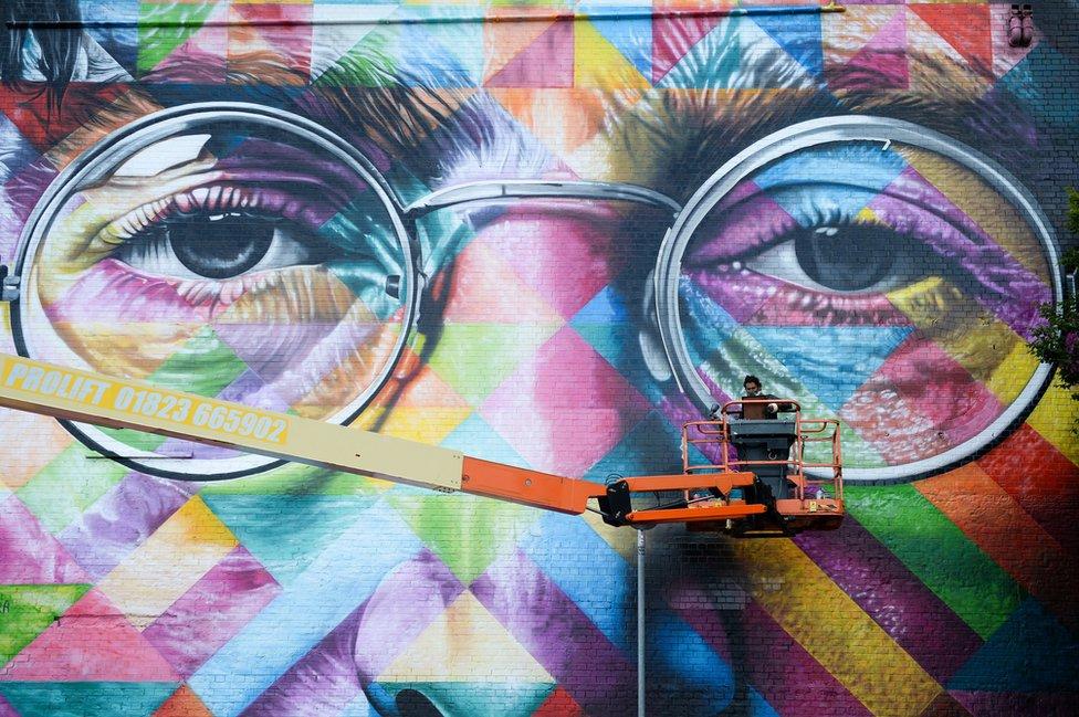 فنان جداري يرسم صورة لجون لينون، أحد مؤسسي البيتلز البريطانية الشهيرة، على حائط كجزء من مهرجان آبفيست للفن الجداري في مدينة بريستول.