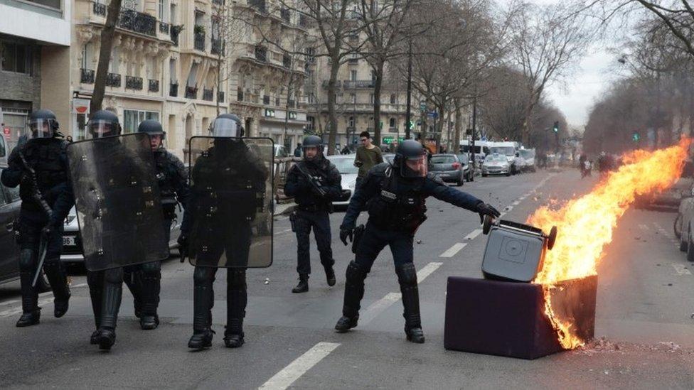 عدد من رجال الشرطة يبعدون صندوق قمامة مشتعل أثناء الاحتجاجات