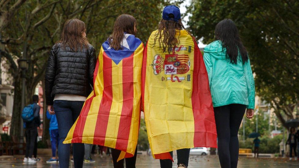 Jóvenes pasean en Figueres con la estelada y la bandera española.