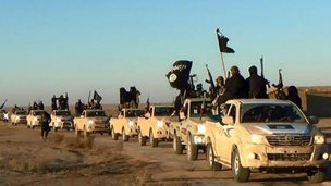 Islamic State militants hold up their weapons and wave flags as they ride in a convoy, which includes multiple Toyota pickup trucks, through Raqqa city in Syria