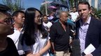 BBC reporter John Suworth (r) talks to a Chinese man and woman watching China's military parade in Beijing