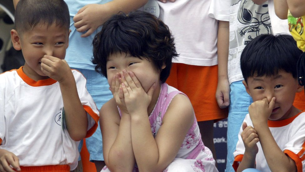 Niños surcoreanos tapándose la boca.