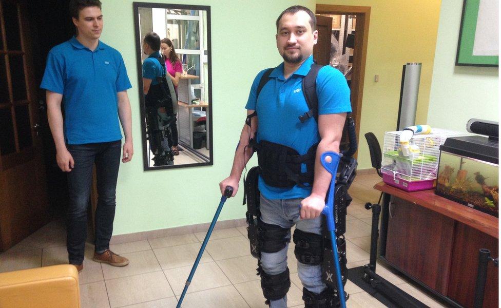 Denis, que está paralizado de la cintura para abajo, muestra el exoesqueleto producido por ExoAtlet.
